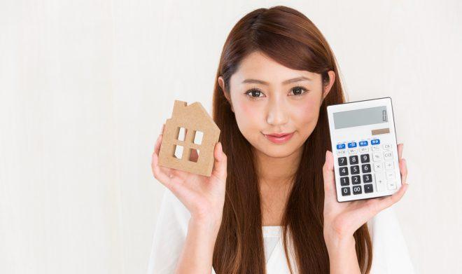 家と電卓を持つ女性