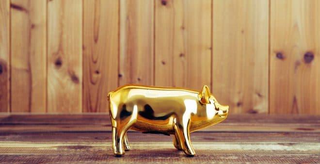 金色の豚の貯金箱と木目の壁