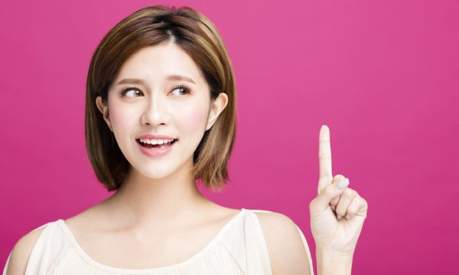young woman pointing to somewhere, isolated on pink background
